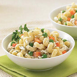 Two bowls of Boursin Garlic & Fine Herbs macaroni salad with olive oil, peas & carrots.